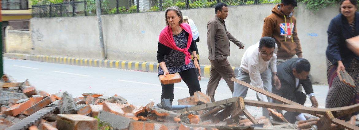 Stanford PhD student Anne Sanquini and Nepalis clear street of bricks from a fallen wall following April 25, 2015, earthquake